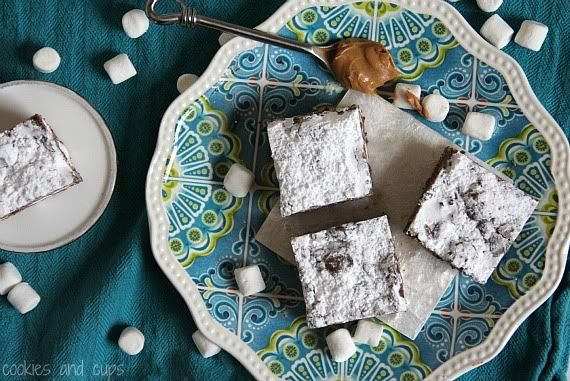 Top view of Puppy Chow Krispie Treat squares topped with powdered sugar on a plate