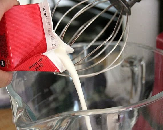 Heavy cream being poured into a stand mixer with whisk attachement