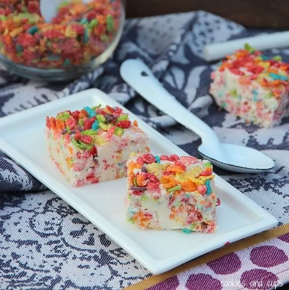 Two squares of Fruity Pebbles fudge on a white rectangular plate
