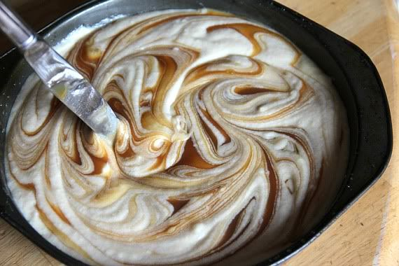 Caramel sauced swirled into vanilla cake batter in a pan