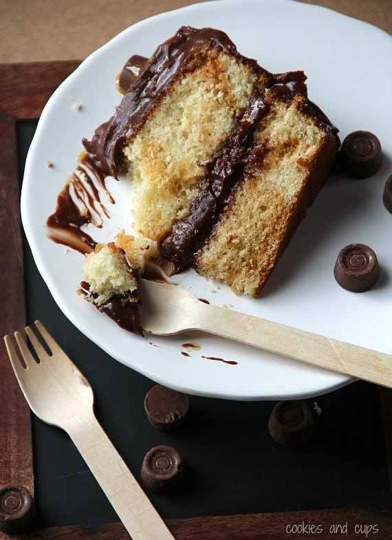 A slice of yellow cake with chocolate frosting on a plate with rolo candies