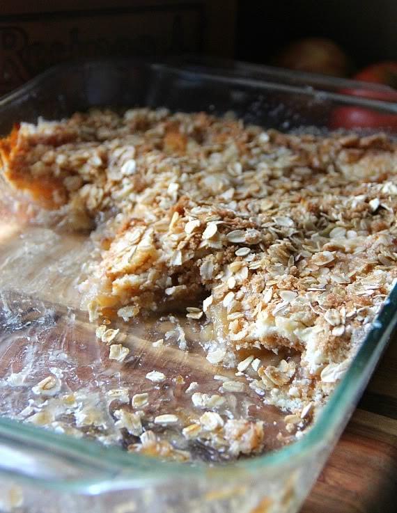 Half-eaten baking dish of oat topped apple pie dump cake
