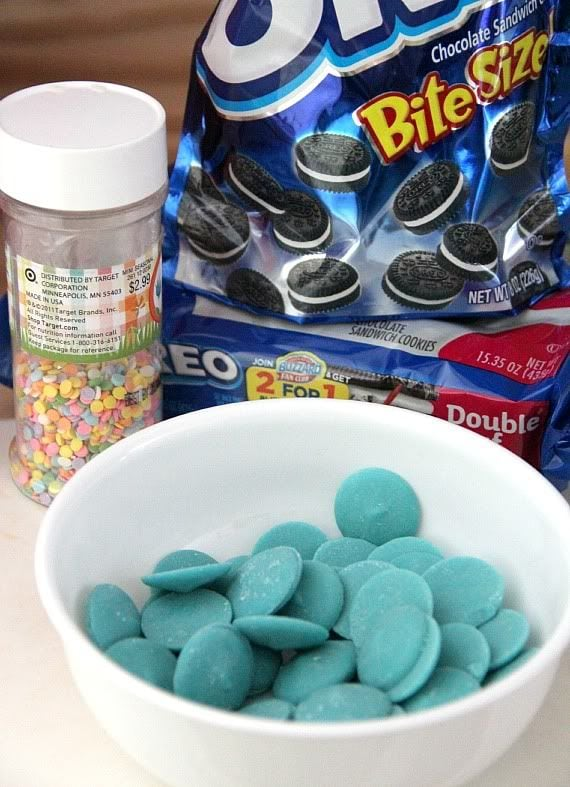 Teal melting wafers in a bowl next to a bag of mini oreos and sprinkles