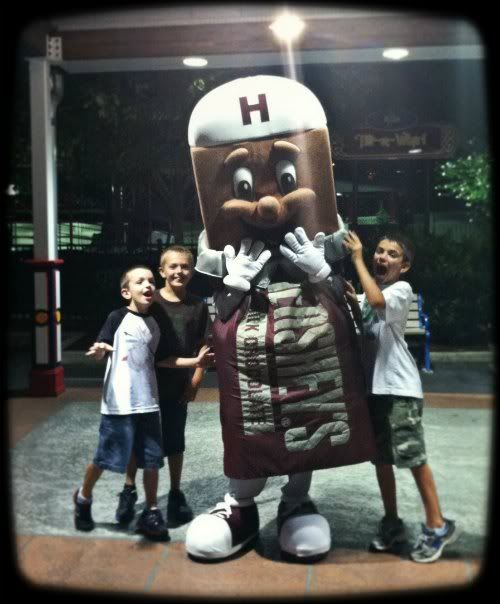 3 boys posing with a Hershey's chocolate bar mascot