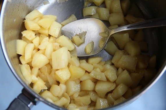 Peeled diced apples cooking in a pan