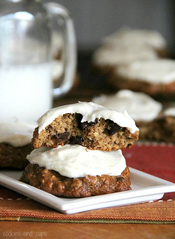 Two banana bread cookies with white frosting on a plate
