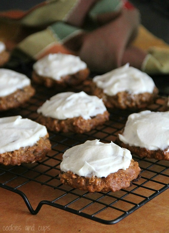 Banana bread cookies with maple cream cheese frosting on a cooling rack