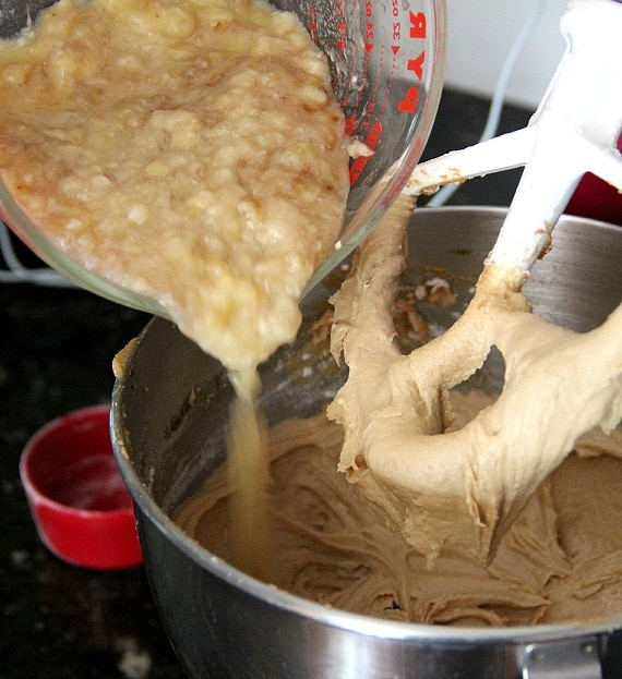 Mashed bananas being added to cupcake batter in a stand mixer bowl