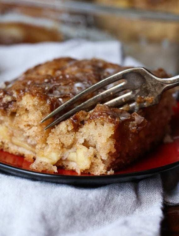 Fork cutting into apple fritter cake