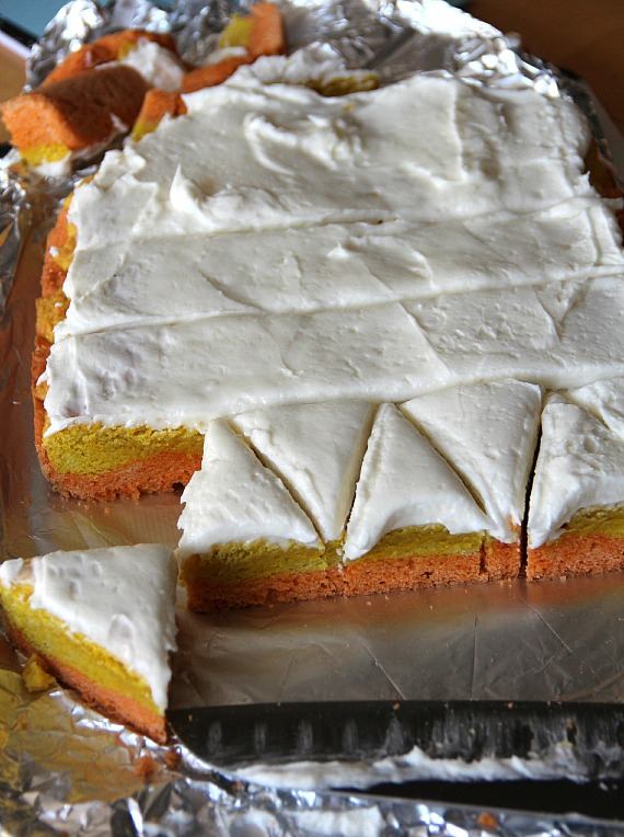 Orange, yellow and white layered frosted cookie bars being cut into triangles