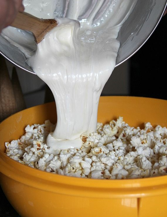 Melted marshmallow being poured over popcorn in a bowl