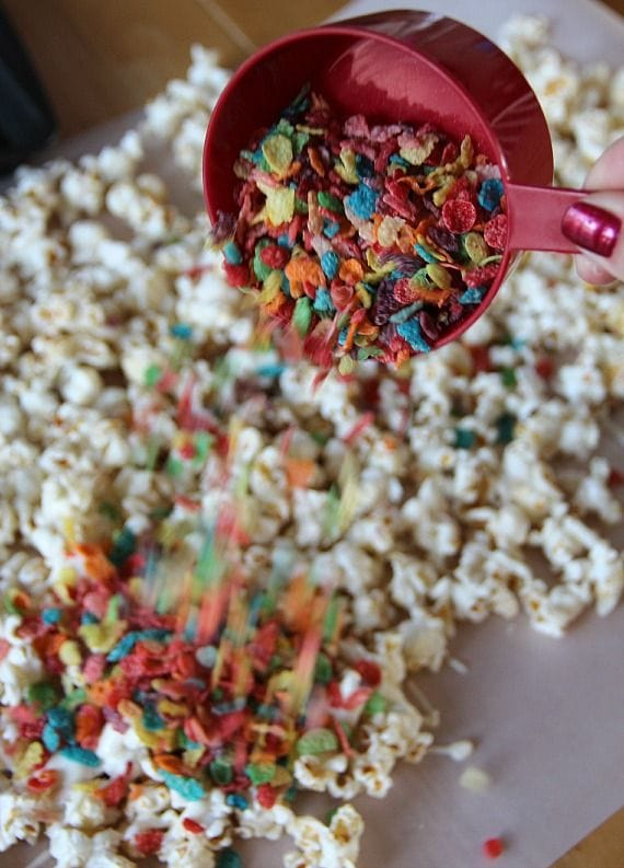 Fruity Pebbles being added to kettle corn with melted white chocolate