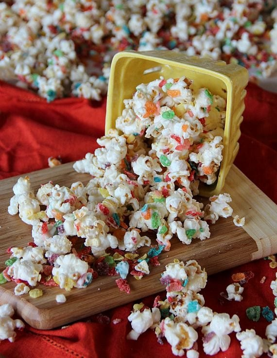 Fruity Pebbles kettle corn spilling out of a yellow carton