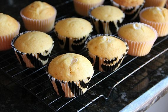 Vanilla cupcakes filled with marshmallow creme on a cooling rack