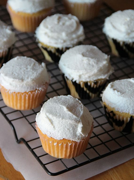 Frosted vanilla cupcakes on a cooling rack