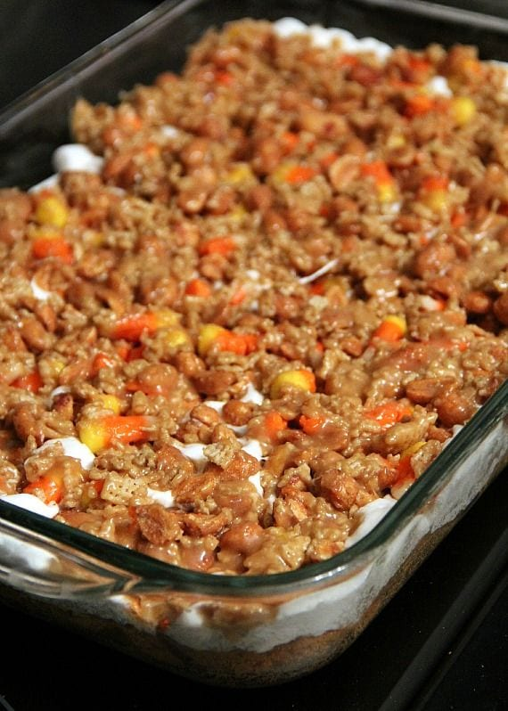 Layered scarecrow bars with crust, marshmallows and candy corn cereal mixture in a 9x13 pan