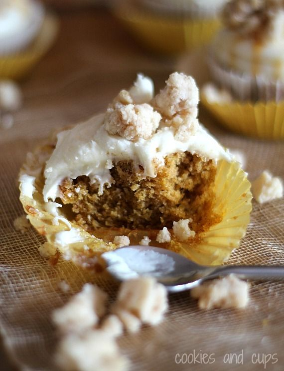 Half of a pumpkin cupcake with cream cheese frosting and streusel topping