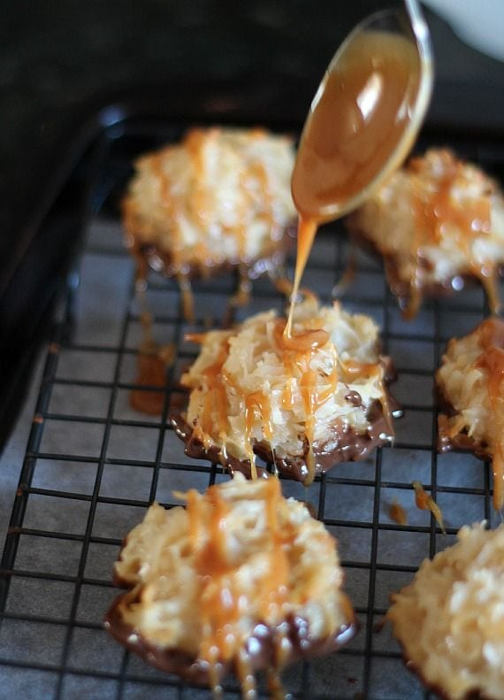 Caramel being drizzled over chocolate dipped coconut macaroons on a cooling rack