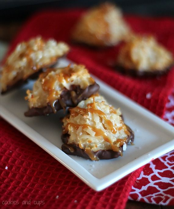 Three chocolate dipped coconut macaroons with caramel drizzle on a plate