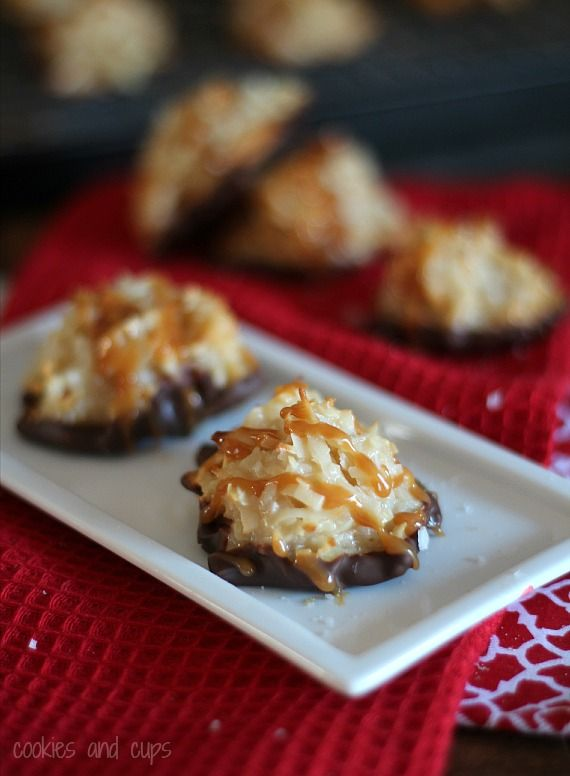 Two chocolate dipped coconut macaroons with caramel drizzle on a plate