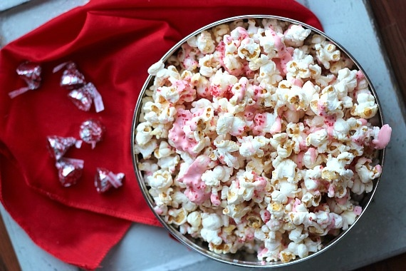 Top view of a bowl of popcorn with melted pink candy cane kiss candy drizzle