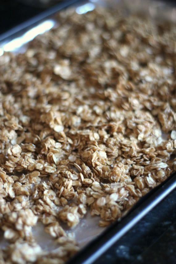 Peanut butter coated oats on a baking sheet