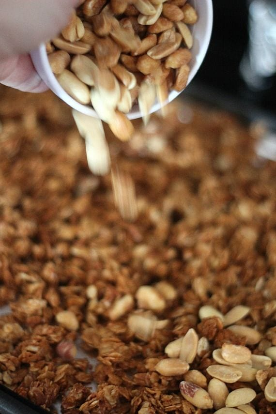 Peanuts being poured into a pan of peanut butter oats