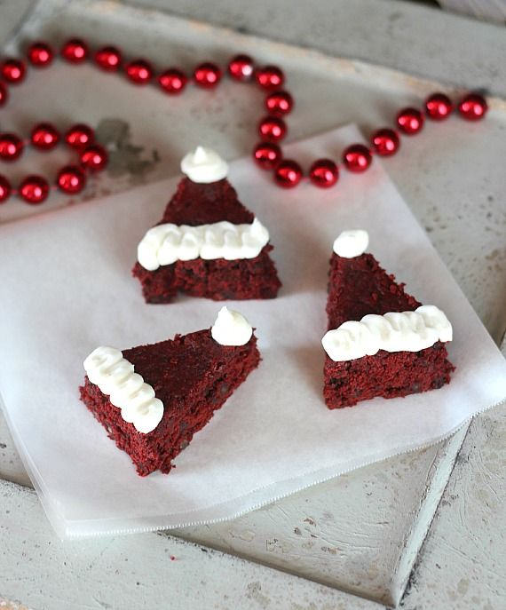 Triangle-shaped Red velvet brownies decorated to look like Santa hats