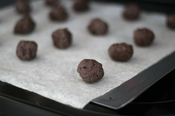 Chocolate cookie dough balls on a parchment-lined baking sheet