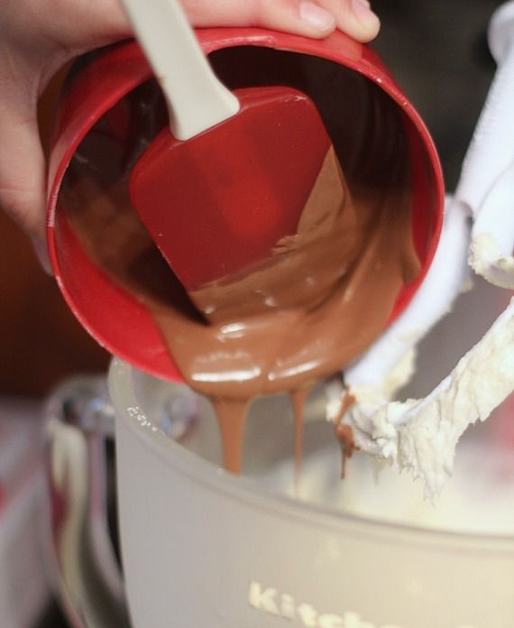 A measuring cup of melted chocolate being poured into a stand mixer bowl