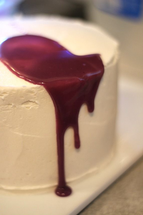 Purple ganache dripping down the side of a white-frosted layer cake