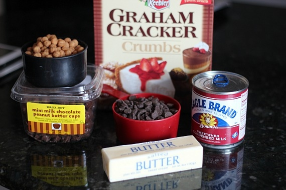 Baking ingredients including graham cracker crumbs, butter, sweetened condensed milk, chocolate chips, butterscotch chips and mini peanut butter cups