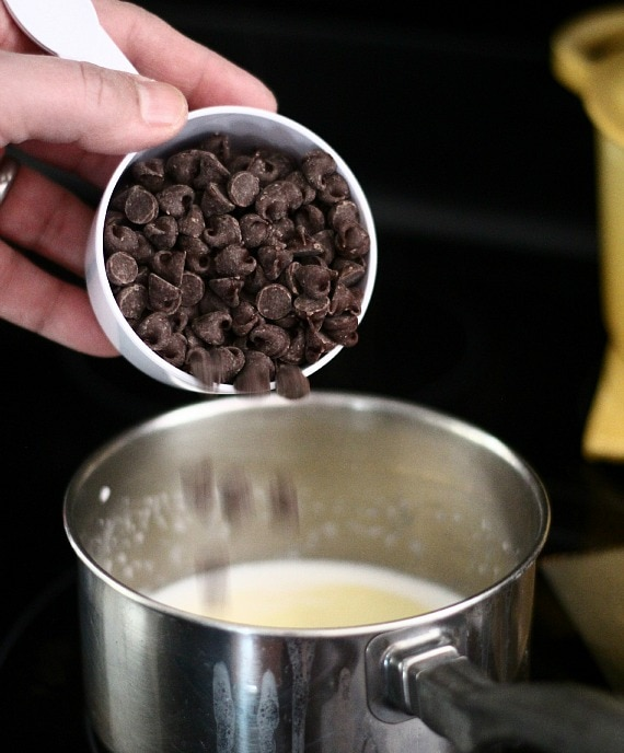 A scoop of chocolate chips being poured into a saucepan