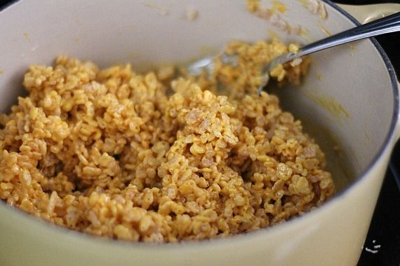 Yellow-tinted rice krispie treat batter in a bowl