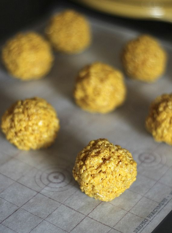 Yellow rice krispie treat balls on a baking sheet