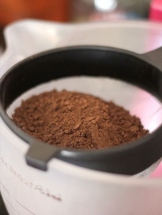 Cocoa powder in a sifter on the edge of a mixing bowl