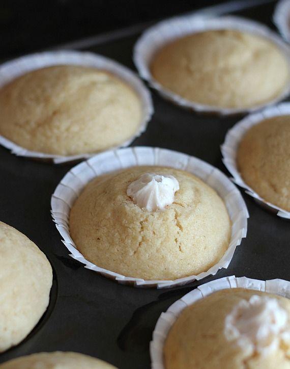 Cream-filled vanilla muffins in a muffin tin