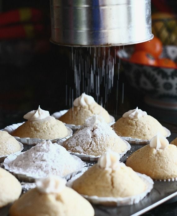 Powdered sugar being sifted over cream-filled vanilla muffins in a muffin tin