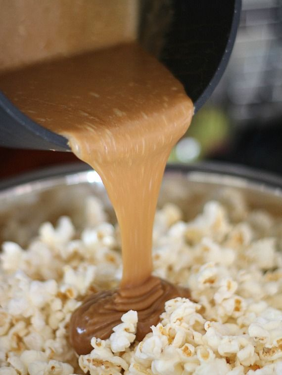 Peanut butter caramel sauce being poured over a bowl of popcorn