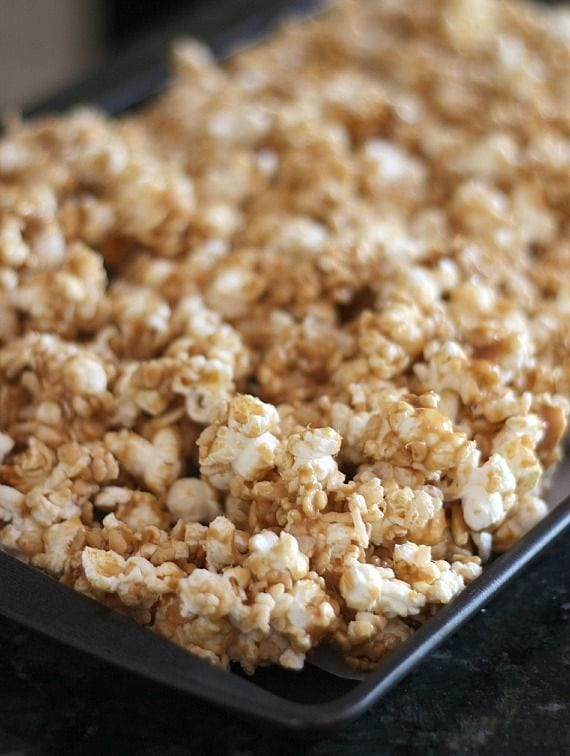 Peanut butter caramel krispie popcorn spread on a baking sheet