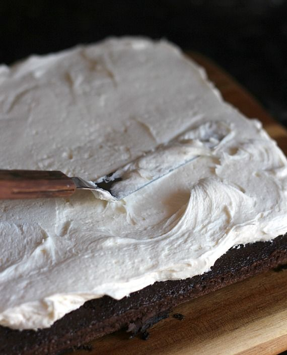 Whoopie pie filling being spread on top of a chocolate cake layer