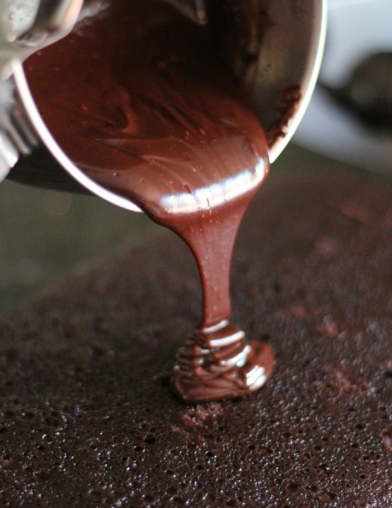 Chocolate ganache being poured over a chocolate cake layer