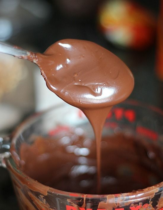 A spoonful of melted chocolate over a liquid measuring cup of melted chocolate