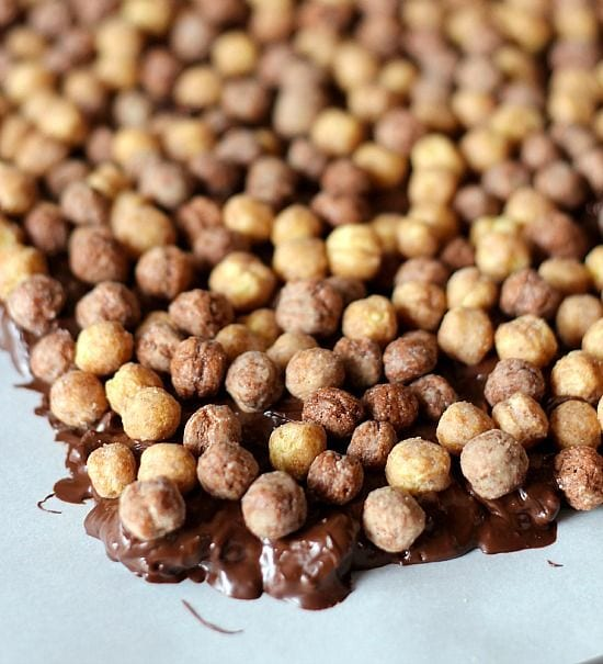 Reeses puffs cereal over melted chocolate peanut butter mixture in a sheet pan