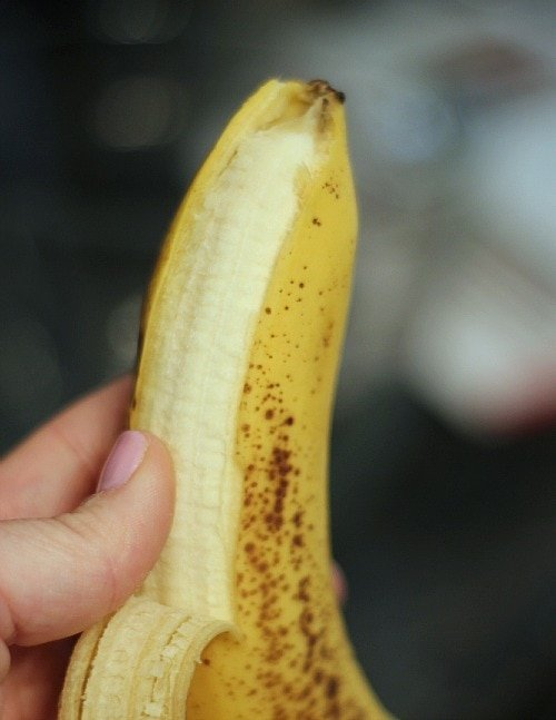 Image of a banana with one strip unpeeled