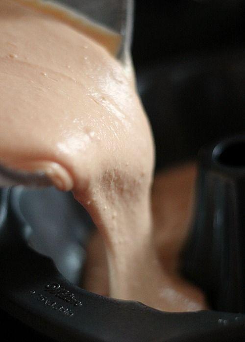 Orange cake batter being poured into a bundt pan