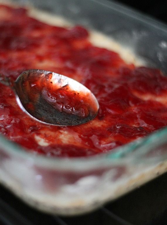 Strawberry jam being spread over a shortbread crust in a 9x13 baking dish
