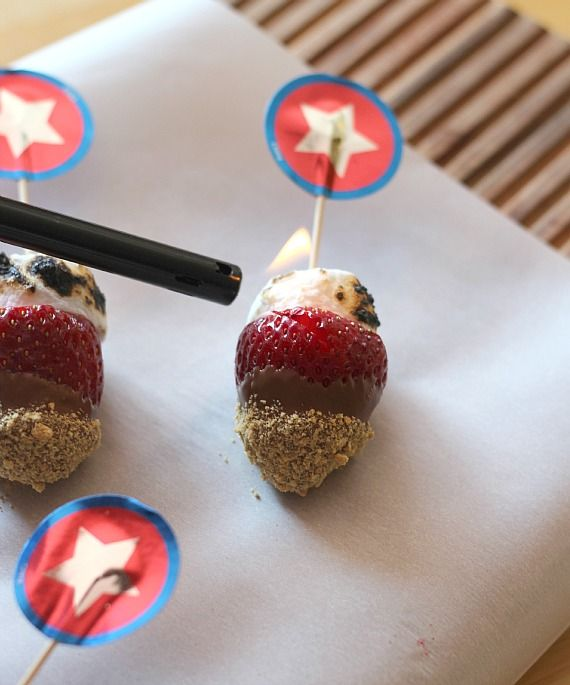 Strawberry S'mores skewers with toasted marshmallows on parchment paper