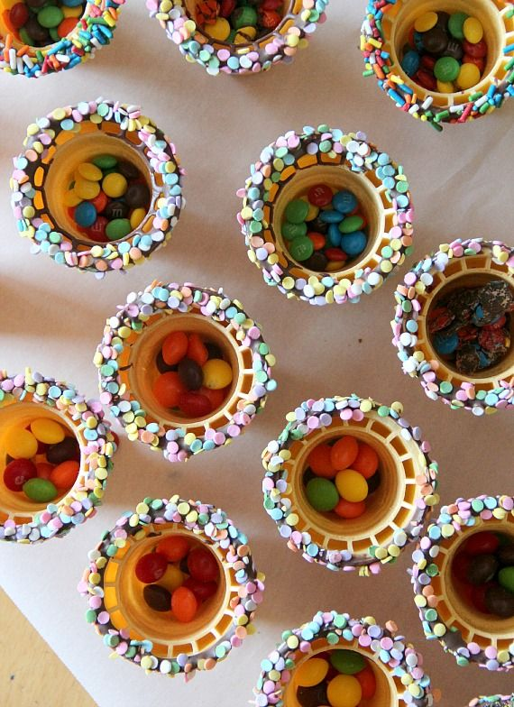Top view of chocolate and sprinkle-rimmed ice cream cones with M&M candies in the bottom