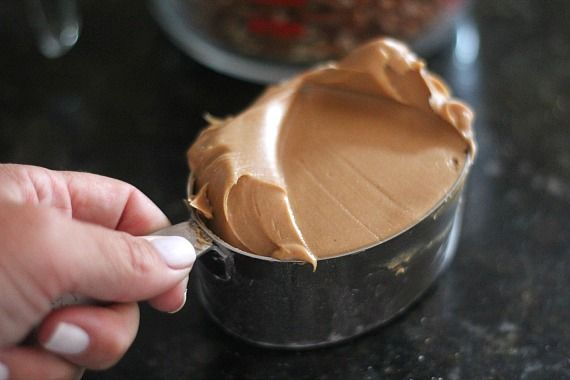 A measuring cup of peanut butter